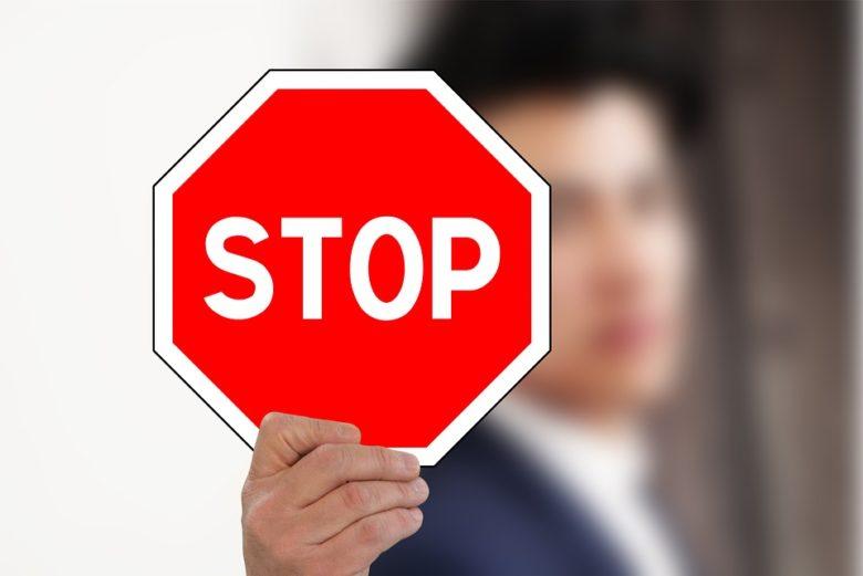 STOPの標識を掲げる男性