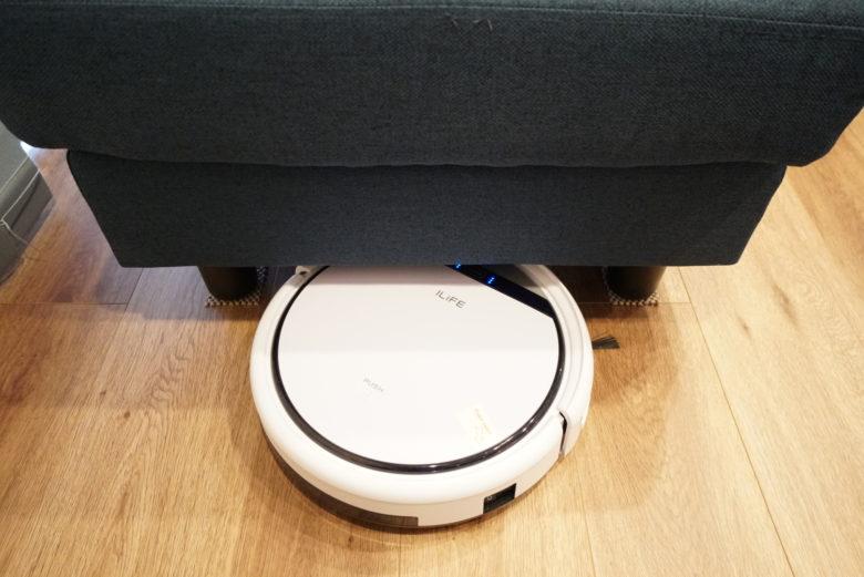 ソファの下を掃除するロボット掃除機